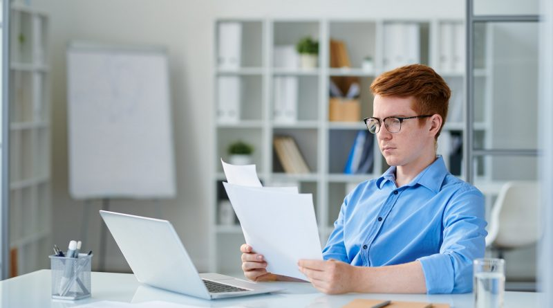 Young serious economist or trader reading financial papers