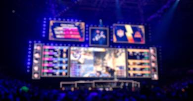 Blurred background of an esports event - Big illuminated main stage of a computer games tournament